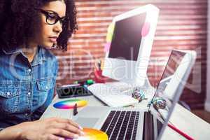 Casual female designer using laptop