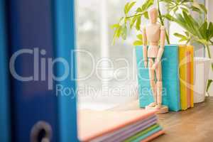 Mannequin and stack of books on wooden window sill