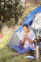 Brunette camper enjoying beverage and sitting in tent