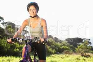 Focused athletic brunette sitting on mountain bike