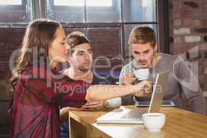Friends having coffee and using laptop together