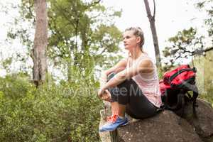 Blonde hiker sitting on rock and viewing the landscape