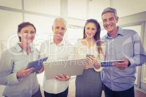 Smiling business people with electronic devices