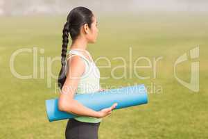 Sporty woman holding exercise mat