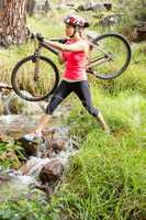 Blonde athlete carrying her mountain bike over stream