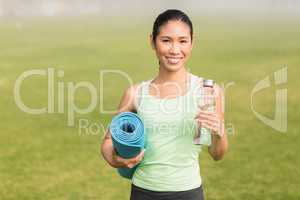 Sporty woman holding exercise mat and water bottle