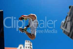 Extreme athlete jumping in the air in front of a building