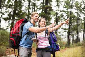 Young happy hikers pointing int he distance