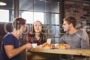 Friends talking and enjoying coffee and croissants