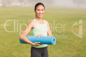 Smiling sporty woman holding exercise mat