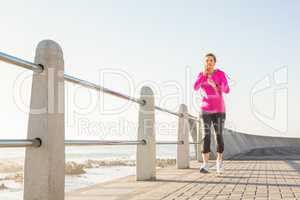 Smiling sporty woman jogging at promenade