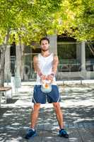 Handsome athlete outfit with a kettlebell