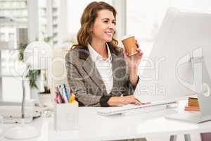 Casual businesswoman working and having coffee
