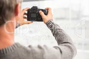 Rear view of man taking pictures with camera
