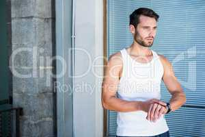 Handsome athlete checking heart rate watch