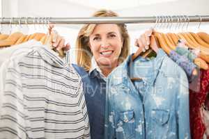 Smiling woman looking through the clothes rail