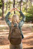 Rear view of blonde hiker framing heart with hands