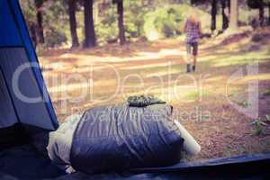 Sleeping bag in front of blonde camper walking away