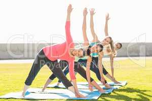 Smiling sporty women doing triangle pose in yoga class