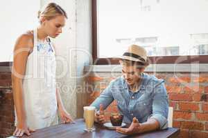 Handsome hipster complaining to blonde waitress