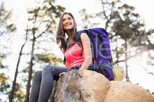 Young happy jogger sitting on rock and looking away