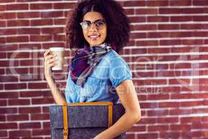 Smiling attractive hipster with felt bag and coffee