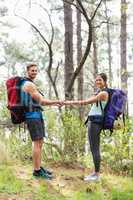 Happy hikers holding hands looking at camera