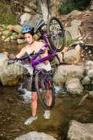 Athletic brunette carrying her mountain bike over stream