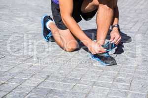 Athlete tying his shoes on a sunny day