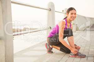 Smiling fit woman tying shoelace at promenade