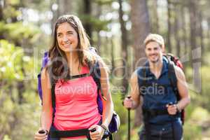 Young happy joggers hiking with trekking poles