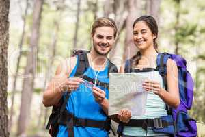 Happy hikers looking at camera holding map and compass
