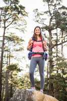 Young happy jogger standing on rock looking at camera
