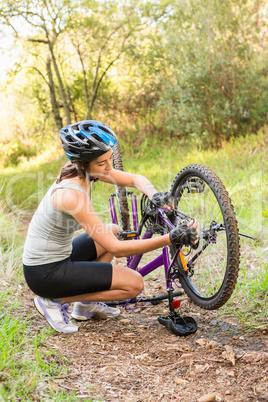 Athletic brunette repairing her mountain bike
