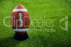 American football standing on holder