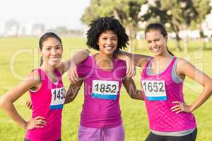 Three smiling runners supporting breast cancer marathon