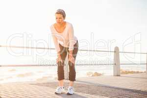 Breathing sporty woman resting at promenade