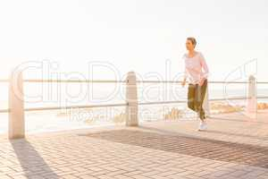 Sporty woman jogging at promenade