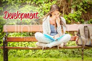 Development against smiling student sitting on bench reading boo