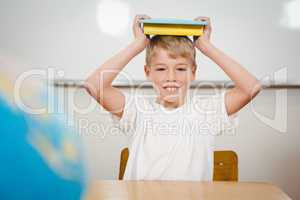 Pupil holding book over his head