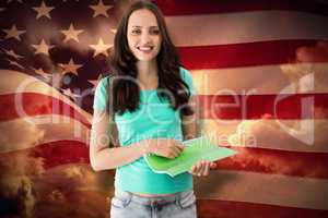 Composite image of portrait of smiling young woman with file