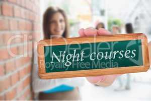 Night courses against pretty student smiling and holding notepad