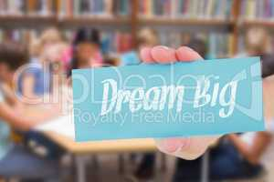 Dream big against cute pupils writing at desk in library