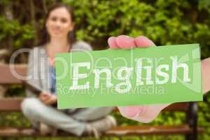 English against smiling student sitting on bench listening music