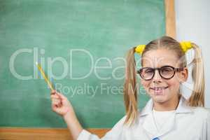 Cute pupil with lab coat pointing on chalkboard