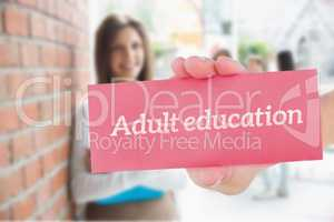 Adult education against pretty student smiling and holding notep