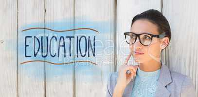 Education against stylish brunette thinking and smiling