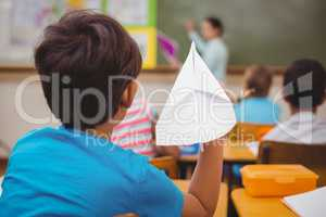 Pupil about to throw paper airplane