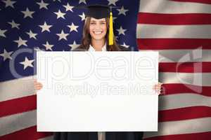 Composite image of a woman in her graduation gown holds a blank