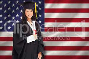 Composite image of a smiling woman holding her degree as she has